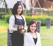 Two confidence business woman working together in a park outd. Two confidence business women is working together in a park outdoor stock photo