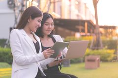 Two confidence business woman working together in a park outd. Two confidence business women is working together in a park outdoor royalty free stock photos