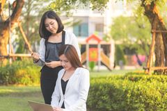 Two confidence business woman working together in a park outd. Two confidence business women is working together in a park outdoor stock photos