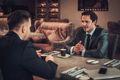 Two confident business men have business lunch at restaurant.  Royalty Free Stock Photography