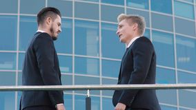 Two confident business men shake hands and begin formal conversation. Two confident business men, meeting outdoors, shake hands and begin formal conversation stock video footage