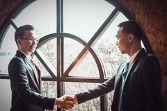 Two confident businessman shaking hands for demonstrating their agreement to sign agreement or contract between their companies. Two confident businessman stock photo