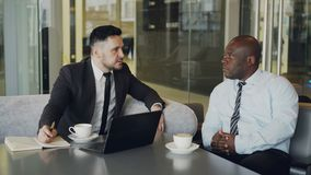 Two confident businessmen discussing about partnership during meeting in modern glassy cafe. Two confident multiracial businessmen discussing about partnership stock video footage