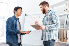 Two confident businessmen making business plan using tablet and flipchart Royalty Free Stock Image