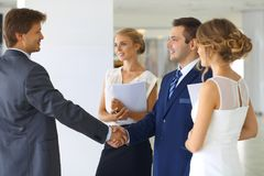 Two confident businessmen shaking hands and smiling while standing at office together with group of colleagues stock image