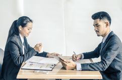Two confident businesspeople using a digital tablet together while working at a table. In a modern office royalty free stock photo
