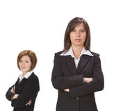 Two confident businesswomen. Isolated against a white background with selective focus on the one Royalty Free Stock Images