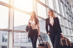 Two confident businesswomen carrying suitcases in airport Stock Photography