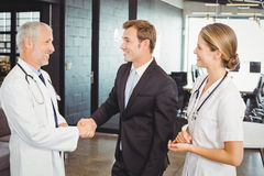 Two confident doctors shaking hands with each other Royalty Free Stock Image