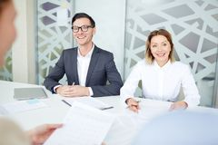 Interview with applicants. Two confident employers talking to applicants during interview in office Stock Photography