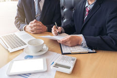 Two confident executives business colleagues meeting and discuss. Ing ideas of project about company offer, they is pointing on a contract and giving stock photos