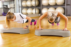 Two Confident Female Friends Doing Pushups In Gym Stock Images