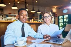 Intercultural associates. Two confident financiers looking at camera while sitting by table in cafe and working with papers Royalty Free Stock Photos