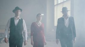 Two confident men in hats and suits and woman in red dress walking forward an abandoned building. The mafia in an empty. Building. Cool guys, thug, mafia stock video