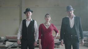 Two confident men in hats and suits and woman in red dress walking toward the camera in an abandoned building. The mafia. Two confident men in hats and suits and stock video footage