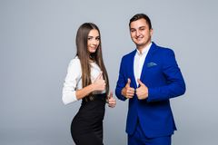 Two confident smiling businesspeople in formalwear showing thumbs-up on gray background. Two confident smiling businesspeople in formalwear showing thumbs-up on Royalty Free Stock Photo