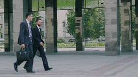 Two confident young businessmen are walking in the urban environment to the office building stock video footage