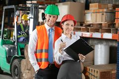 Two Confident Young Supervisors At Warehouse. Portrait of two confident young supervisors with book clipboard at warehouse Stock Photography