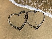 Two connected Hearts drawn on the beach sand with sea waves stock image