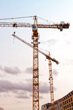 Two construction cranes. Two yellow construction cranes on the sky Stock Images