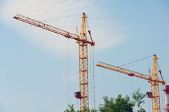 Two construction cranes against  blue sky Stock Photography