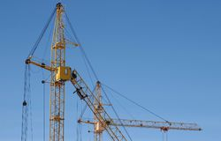 Two construction cranes against the sky background. royalty free stock image