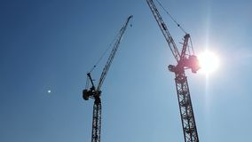 Two construction cranes on the background of blue sky and the sun, which shines in the camera hiding behind the. Construction crane stock video