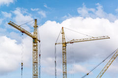 Two construction cranes on  blue sky background Royalty Free Stock Photos