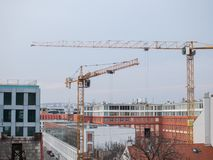 Two construction cranes in city surrounded by modern buildings. Apartment building with offices under construction stock photos