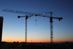 Two construction cranes with gradient sunset sky royalty free stock photography