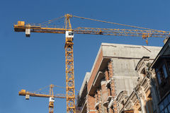 Two construction cranes and house under construction Stock Photo