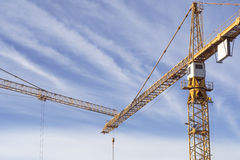 Two construction cranes meeting against blue sky. Stock Images