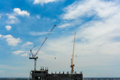 Two construction cranes on unfinished hotel Royalty Free Stock Photography