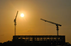 Two construction cranes at work against the evening sky Stock Photo