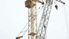 Two construction cranes working on a construction site. Winter stock footage