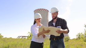 Two engineers in helmets with drawings in outdoors. Two construction engineer man and woman in white protective helmets are working with the drawings on the stock video