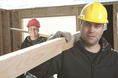 Two construction  men working outside. Building a house with piece of wood Stock Photography