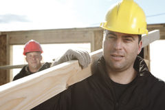 Two construction  men working outside. Building a house with piece of wood Stock Images