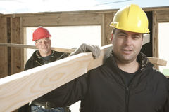 Two construction  men working outside. Building a house with piece of wood Royalty Free Stock Photography