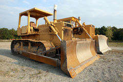 Two construction vehicles. Close up of two yellow construction diggers parked beside each other Stock Image