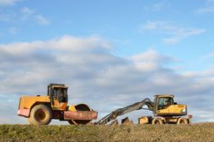 Two construction vehicles on uncultivated terrain stock photos