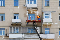 Two construction workers in bucket of crane vehicle are reconstructing the facade of building in Moscow Royalty Free Stock Photography