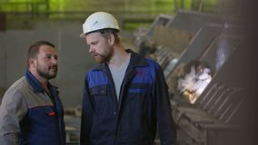 Two construction workers discuss stages of construction in heavy industry factory stock footage