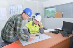 Two construction workers discussing plans. Amending stock images