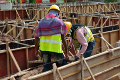 Two construction workers fabricating ground beam formwork Royalty Free Stock Photography