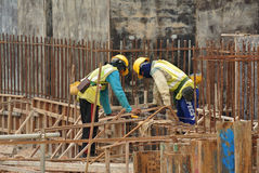 Two construction workers fabricating ground beam steel reinforcement bar Stock Images