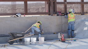 Two Construction Workers Finish Concrete Work. Near the border stock video footage