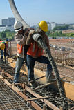 Two Construction Workers Using Hose from Concrete Pump Royalty Free Stock Photos