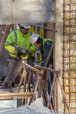 Two construction workers are working with a drill bit stock images