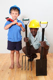 Two Constuction workers. Old african men with a hard-hat holding a fork and shovel,youn boy with hard-hat and wrench over his shoulder royalty free stock photography